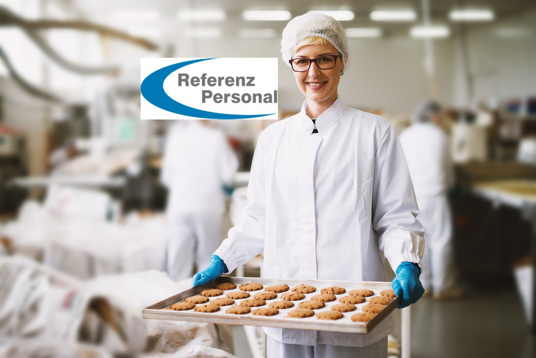 Young satisfied female worker in sterile clothes holding fresh made cookies in food factory.